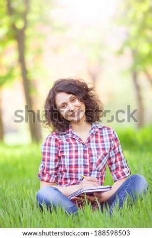 Indian girl with notebook in the park.