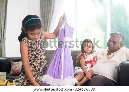 indian grand daugther trying out diawli dress for the grandfather - stock photo