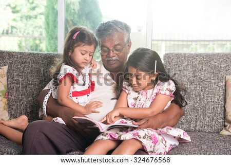 indian grandfather learning with his granddaughters - stock photo