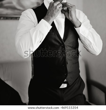 Indian groom with white cravat getting ready on wedding day