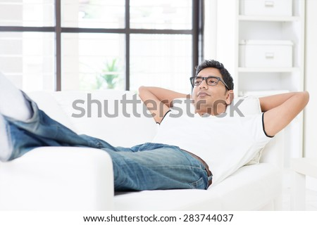 Indian guy resting and daydreaming at home. Asian man relaxed and lying on sofa indoor. Handsome male model.