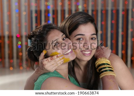 Indian Hindu bride with turmeric paste on her face hugging sister. - stock photo