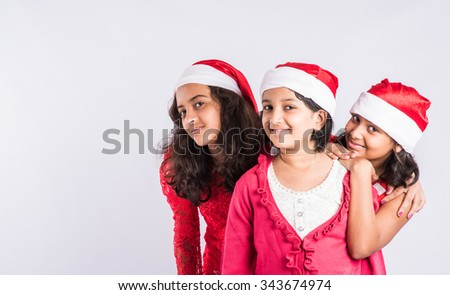indian kids celebrating christmas, 3 indian teenage girls, posing, white background, asian girls and christmas, indian girls and christmas, santa hat, closeup - stock photo