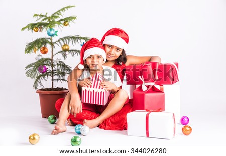 indian kids in christmas time, indian boy sitting in elder sister's lap, santa hat, christmas and india, indian christmas, christian, asia and christmas, christmas tree, gift boxes, isolated on white - stock photo