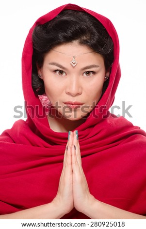Indian lady dressed in traditional red-coloured sari with her hands clasped is ready for having the deep pray. She is going to pray for her country. - stock photo