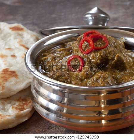 Indian lamb korma curry in traditional copper bowl, with naan bread. - stock photo