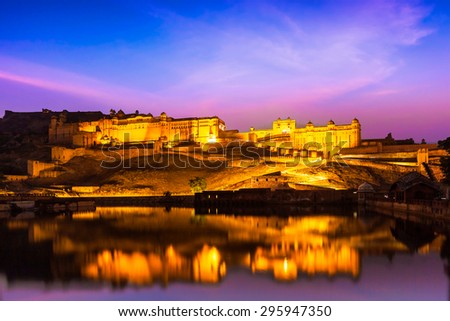 Indian landmark - Amer Fort (Amber Fort) illuminated at night - one of principal attractions in Jaipur, Rajastan, India refelcting in Maota lake in twilight - stock photo