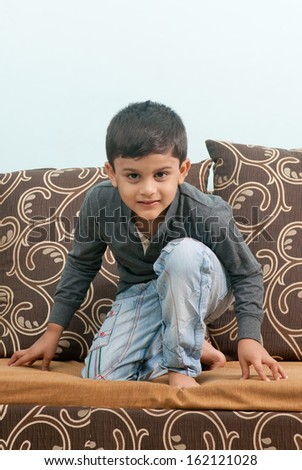 Indian little boy get set ready play on bed