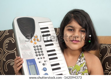 Indian little girl with musical instrument piano