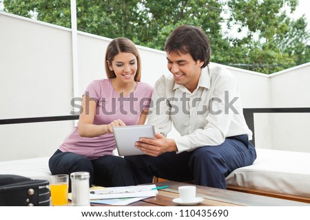 Indian male architect having discussion with female client over a digital tablet - stock photo
