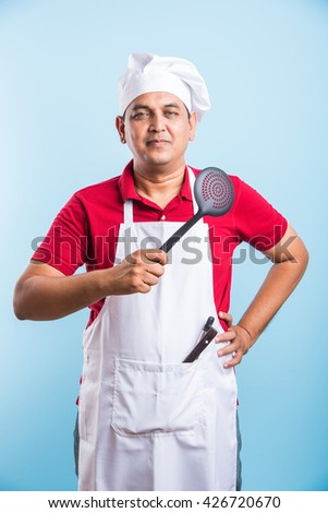 indian male Chef Holding spoon skimmer Isolated On blue Background, asian male chef holding spoon - stock photo