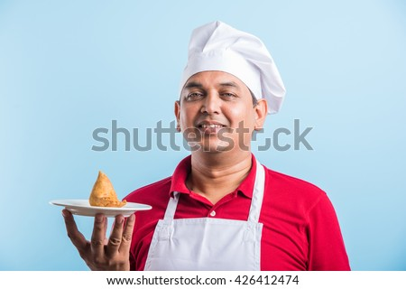 indian male chef tasting indian snack samosa, asian male chef cook and food in plate - stock photo