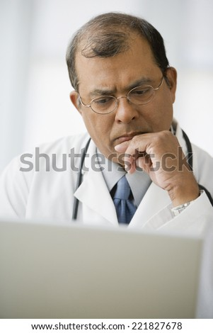 Indian male doctor looking at laptop - stock photo