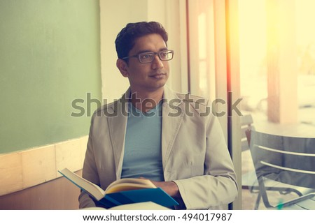 indian male reading book at cafe