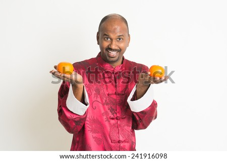 indian male with chinese new year clothes and mandarin oranges - stock photo