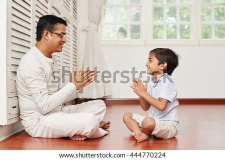Indian man and his son sitting on the floor and playing together - stock photo