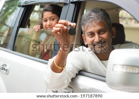 Indian man buying new car and showing the key, sitting in car. Asian family lifestyle. - stock photo