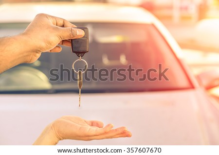 Indian man giving modern car keys ready for rental - Concept of transportation with automobile second hand sale and trade - Warm filtered look with artificial sunlight - Focus on hand keys - stock photo