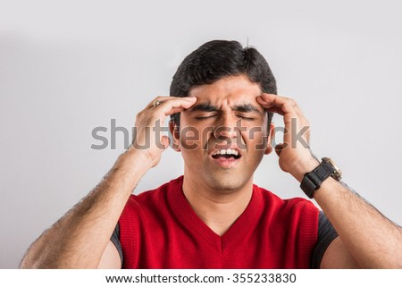 indian man having a headache, asian man having a headache, Frustrated indian man with a headache, Negative human emotion facial expression feelings. massaging forehead with hand - stock photo