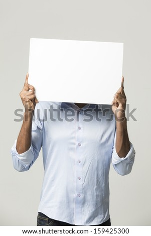 Indian man holding up a banner against a grey background. Cardboard placard is blank ready for your message.