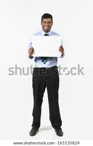Indian man holding up a banner. Cardboard placard is blank ready for your message.  - stock photo
