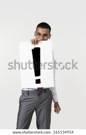 Indian man holding up a banner with an explanation mark