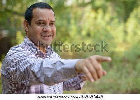 Indian man in park pointing finger