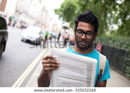 indian man in the street reading a newspaper - stock photo