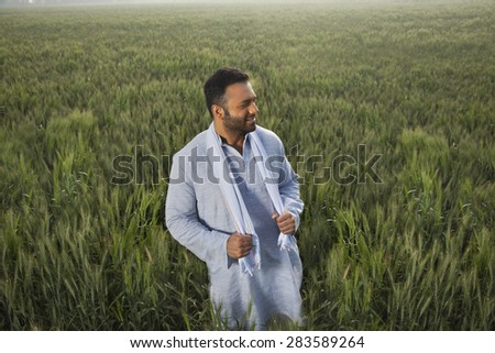 Indian man looking away while standing in a field - stock photo