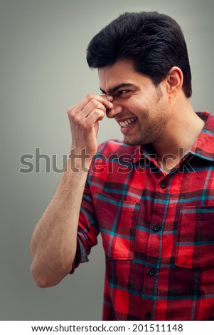 Indian man looking happy and making laugh with touching nose
