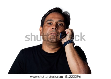 Indian man on hold, talking on a cell phone. Isolated image