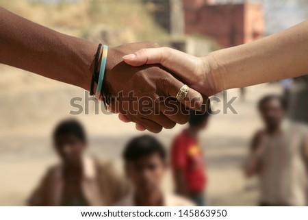 Indian man shaking hands with tourist, India - stock photo