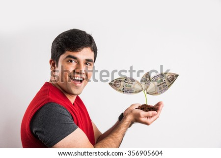 indian man surprised to see money grown on tree, asian man with monet plant, indian young man with money plant, indian paper currency growing on tree, happy indian man, isolated on white background - stock photo
