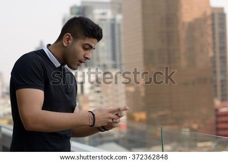 Indian man using mobile phone - stock photo
