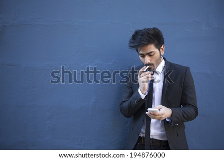Indian man with a smartphone & cigarette. Asian business man using smartphone, leaning against a blue wall. - stock photo