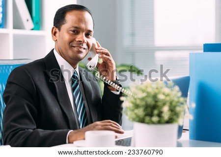 Indian manager talking on the telephone at his workplace - stock photo