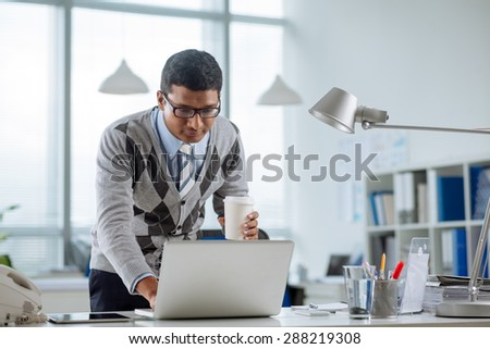 Indian manager with a coffee cup looking at laptop screen