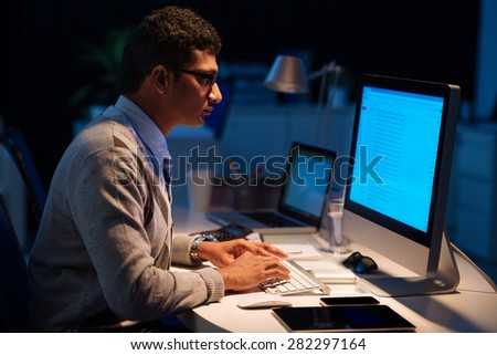 Indian manager working in the office late at night - stock photo