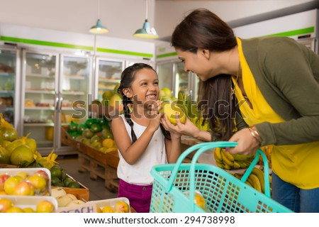 Indian mother and daughter choosing fruits at the grocery store - stock photo