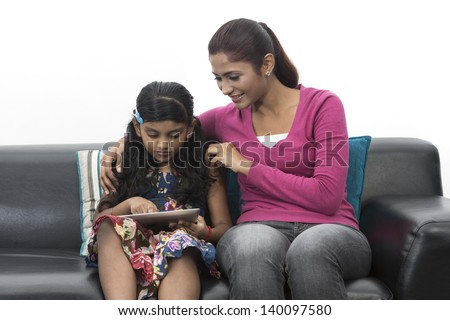 Indian Mother And Daughter Using digital touchpad At Home on sofa - stock photo