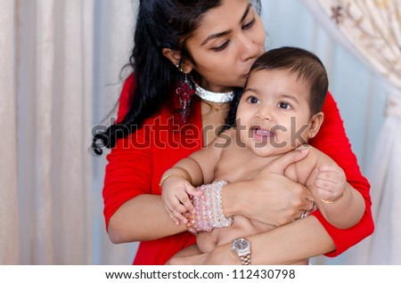 Indian mother kissing her baby girl, indoor - stock photo