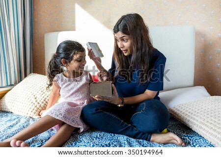 Indian mother open up present box with her daughter - stock photo