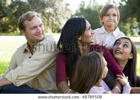 Indian mother surrounded by beautiful mixed race family - stock photo