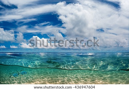 Indian ocean half water shoot. Daylight in Sky and underwater shallow sandy bottom  discovered. - stock photo