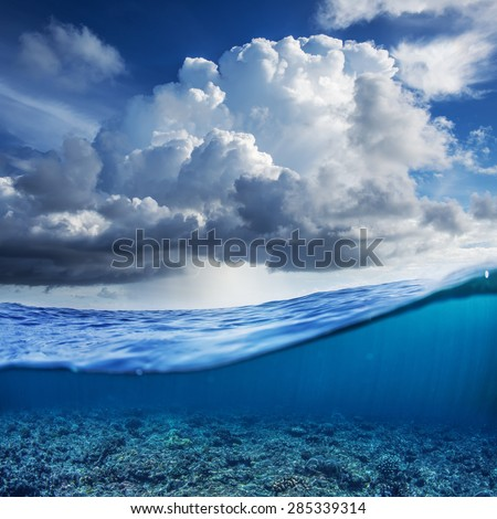 Indian ocean half water shoot with cloudy sky and underwater world discovered - stock photo
