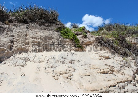 Indian Ocean waves rolling onto the  sand  mixed with black ilmenite deposits at Hutt's Beach near Bunbury Western Australia  have eroded the sandy dunes during a spring storm. - stock photo