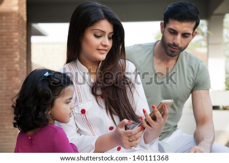 indian or multi ethnic family , mother showing something to her daughter on Phone tablet - stock photo