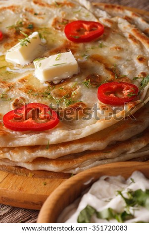 Indian paratha with butter and herbs macro on the table. vertical