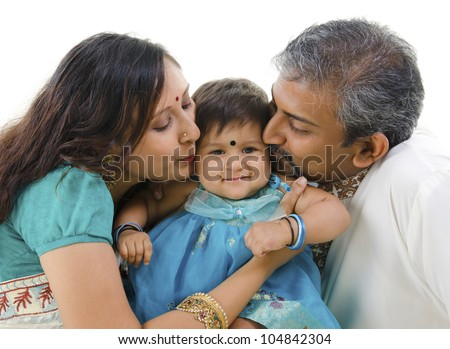 Indian parents giving their daughter a kiss, isolated on white background