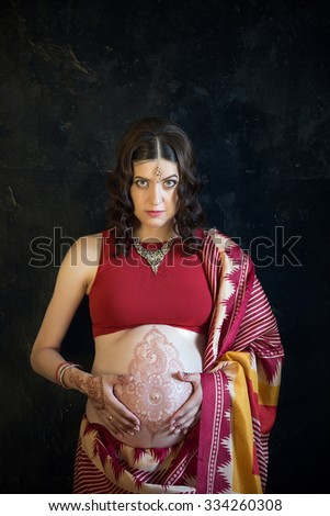 Indian picture on woman hands and pregnant belly with henna tattoo on dark wall background
